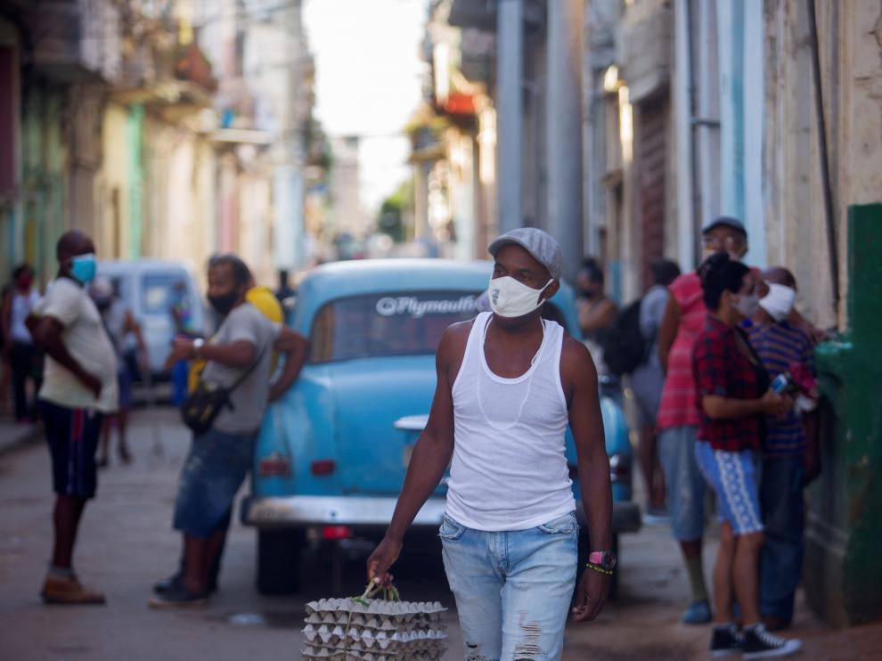 Un hombre camina por una calle con cubetas de huevos en La Habana.