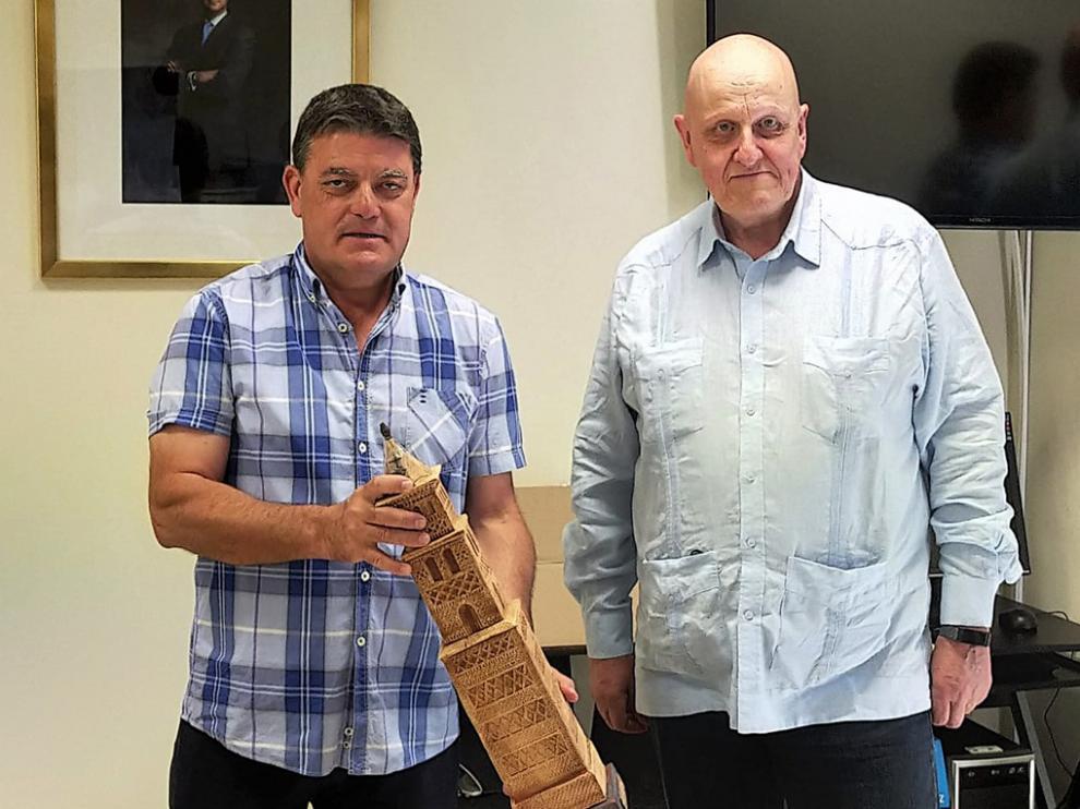 Leontxo García firmó en el libro de honor del ayuntamiento de Alcubierre y su alcalde le entregó una reproducción de la torre mudéjar de la iglesia