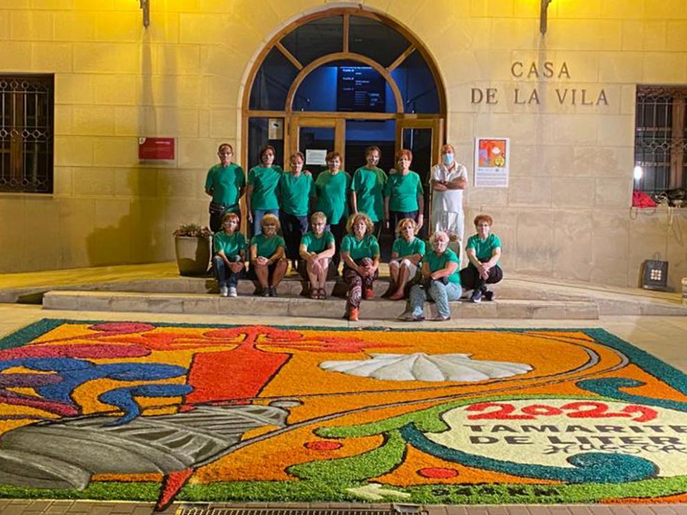 Grupo de alfombristas junto a la alfombra conmemorativa del Año Jacobeo 2021, en la plaza de España de Tamarite.