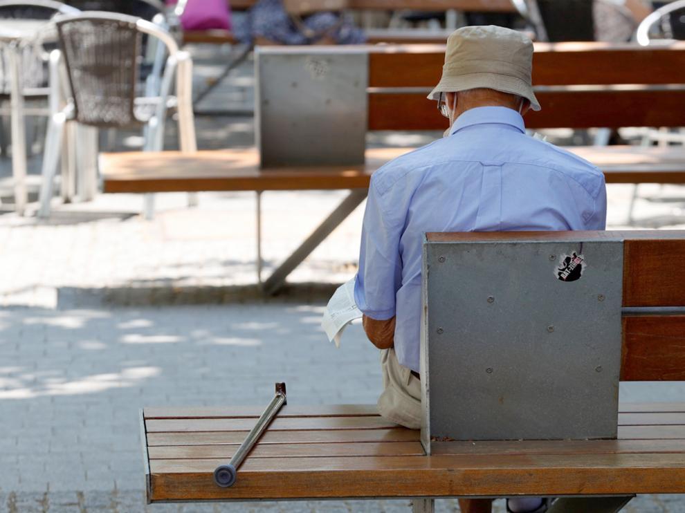 Una persona mayor ojea el periódico en uno de los bancos de Madrid Río, este lunes, cuando se celebra el Día de los Abuelos