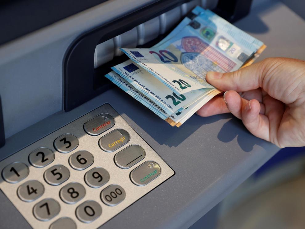 Una persona saca dinero de un cajero de una entidad bancaria