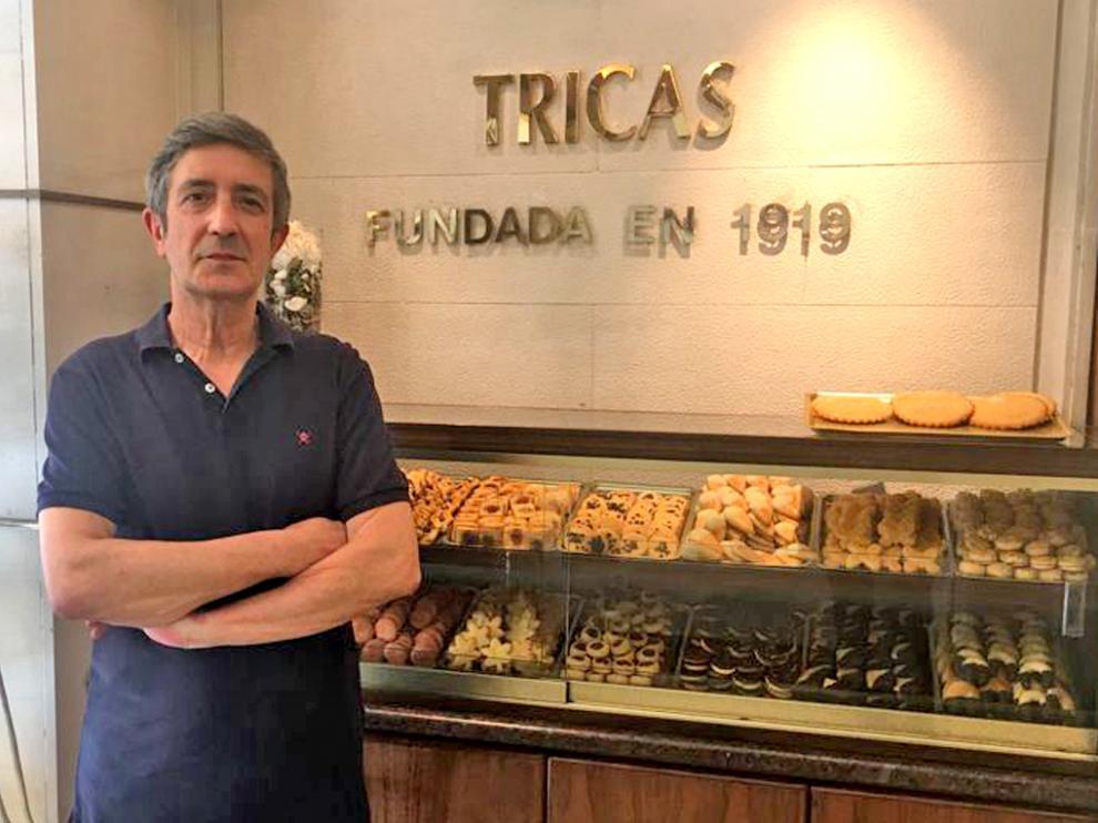 Manuel Tricas Benito junto al rótulo que recuerda el año de fundación del establecimiento