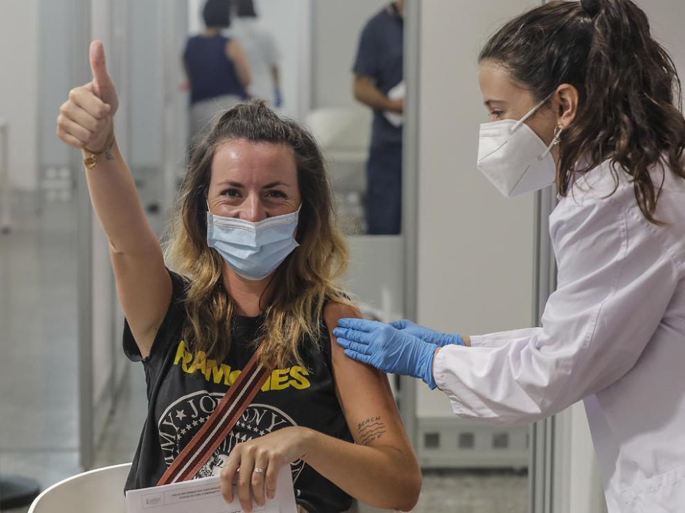 Una joven sonríe y saluda mientras recibe la vacuna contra la Covid-19 en la Ciutat de les Arts i les Ciències de Valencia