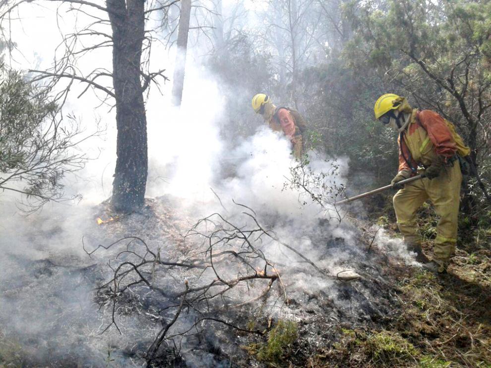 Trabajos de una cuadrilla de bomberos en la extinción de un incendio forestal en Aragón