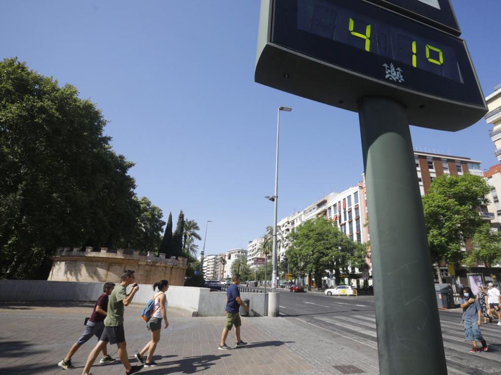 Unas personas caminan por una calle del centro de Córdoba junto a un termómetro que marca 41 grados