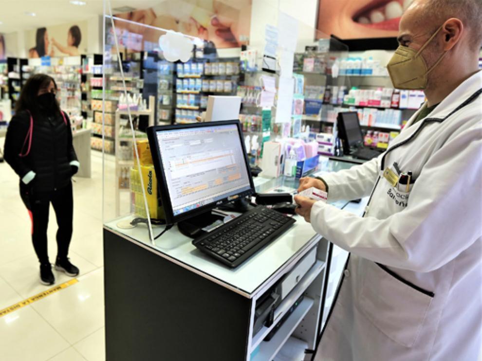 Un profesional de la farmacia Barreña, situada en la ciudad de Huesca, atiende a una clienta.