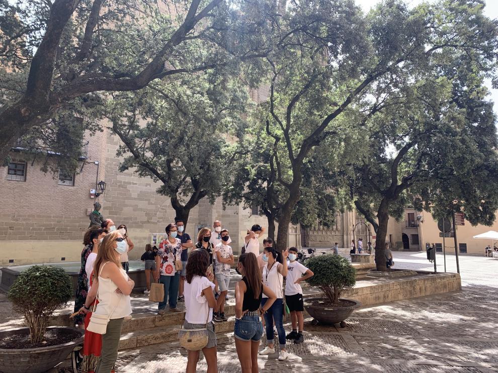 Grupo de turistas frente al Ayuntamiento de Huesca en una visita guiada a la ciudad