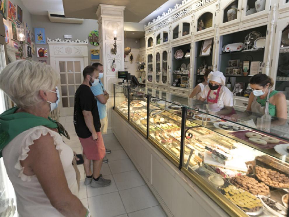 Clientes de la Pastelería Vilas en la capital de Huesca compran los productos típicos de temporada.