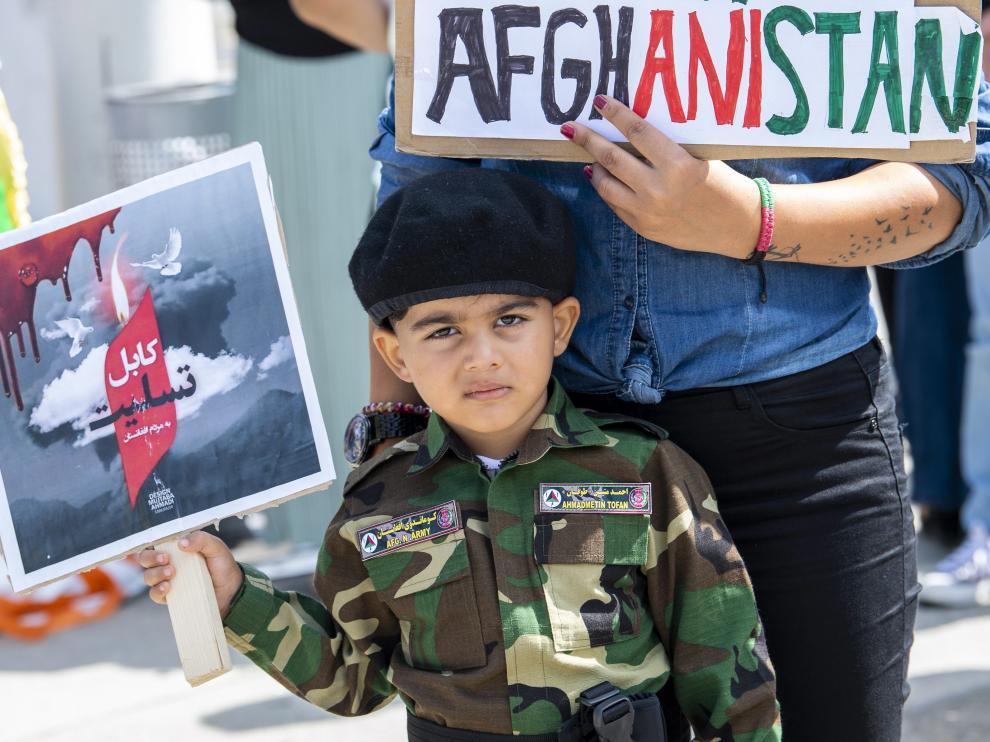 Un niño muestra una pequeña pancarta en apoyo a Afganistán.
