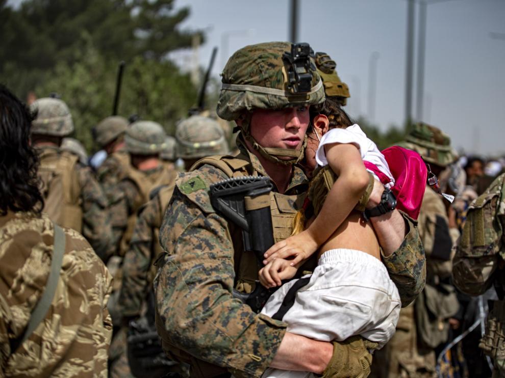 Un soldado transporta a un bebé en Afganistán.