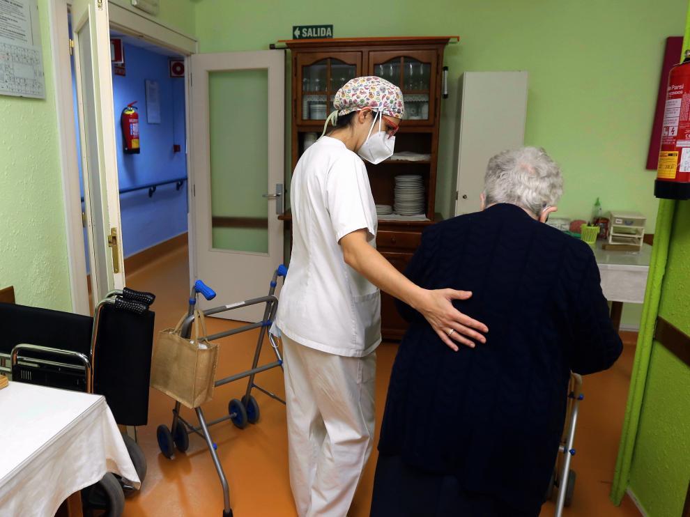 Trabajadora de la residencia Avenida, de Huesca, ayuda a una residente a desplazarse.