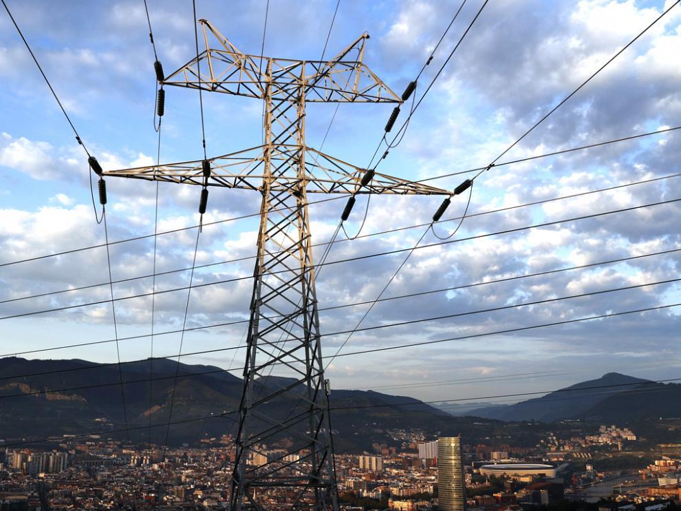 Una torre de transporte de energía perteneciente a red eléctrica, con la ciudad de Bilbao al fondo