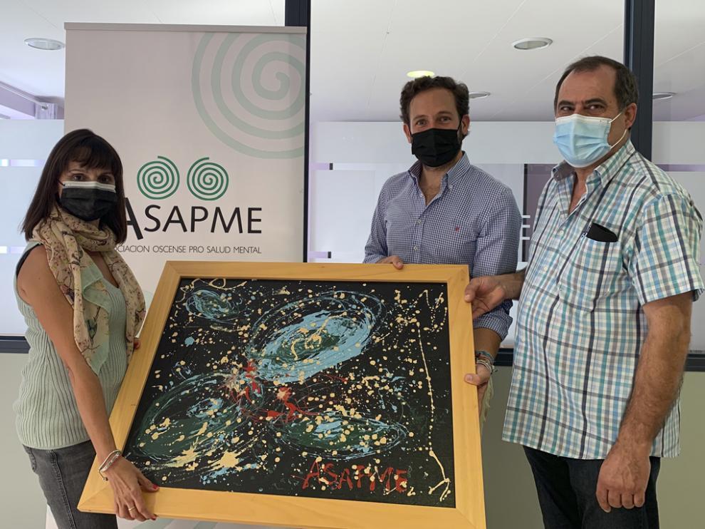 Lucía Mur entrega el lienzo a Isaac Claver, en presencia de Salvador Sarrado.