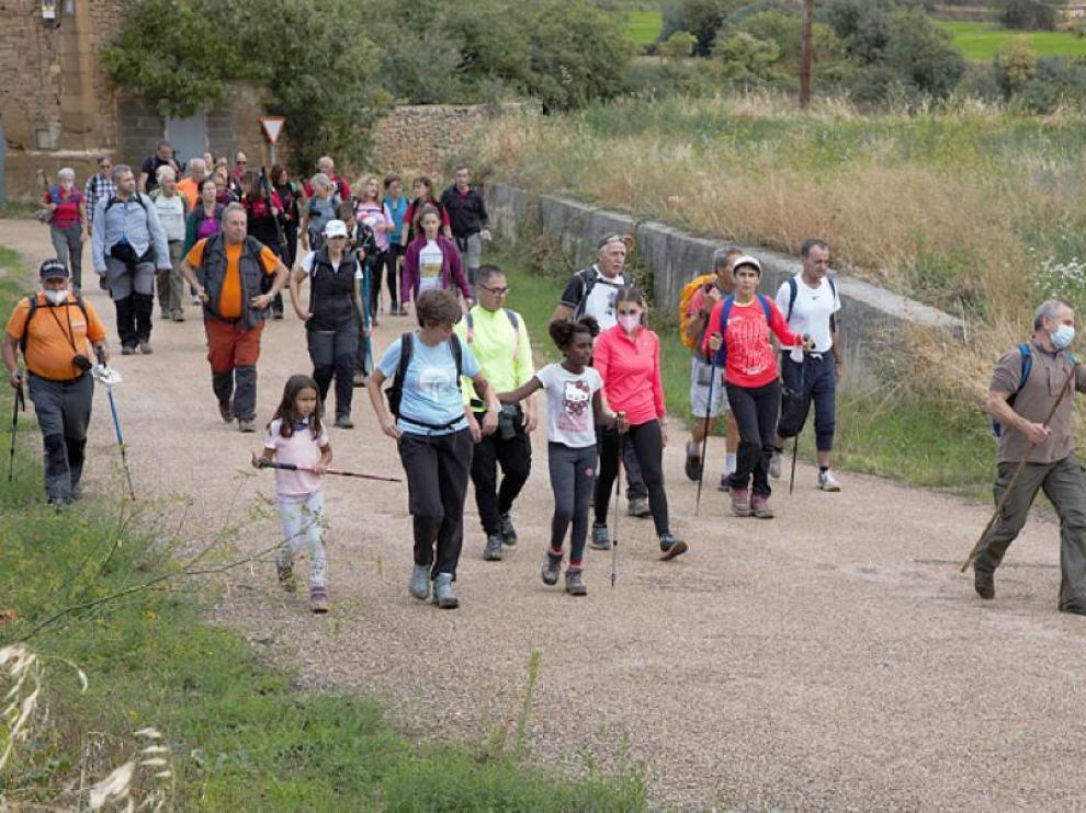 Múltiples integrantes de la caminata a su paso por el municipio de Barluenga, uno de los tramos del recorrido.