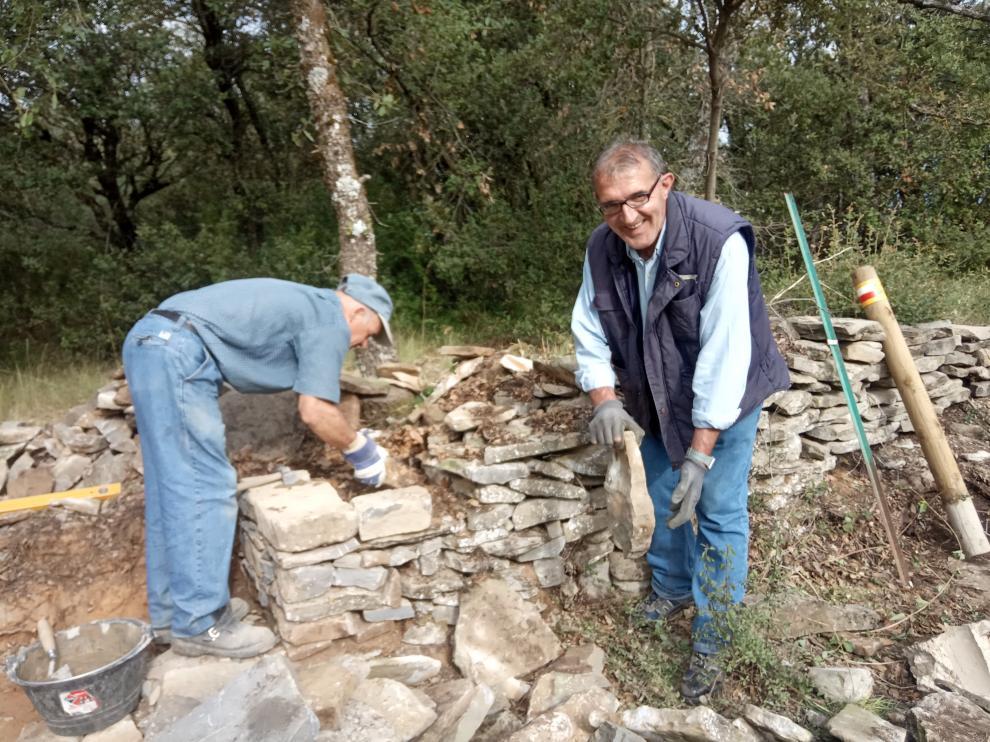 José María, de Casa El Herrero, e Ismael, de Casa El Baile, se afanan en la reconstrucción del muro.