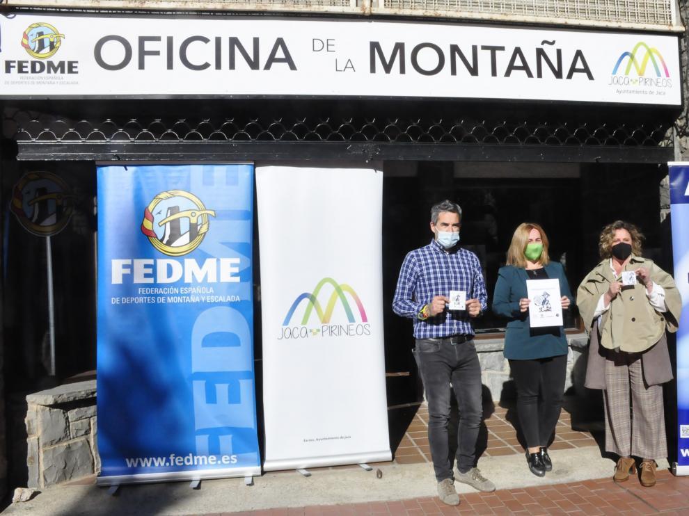 Íñigo Ayllón, Olvido Moratinos y Marian Bandrés muestran el cartel y las pegatinas que se repartirán en comercios de Acomseja.